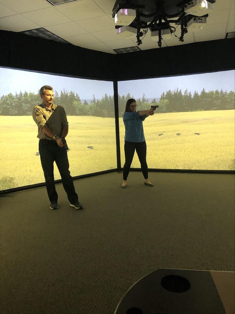 Sarah and Brian in the simulated shooting range with video screens