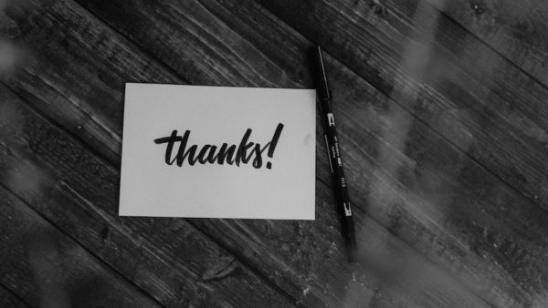 """Table with notecard saying """"thanks!"""" with pen next to it."""