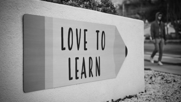 """A man walks on the sidewalk past a sign shaped like a pencil that says """"Love To Learn"""""""