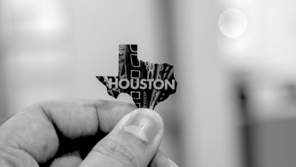 """A hand holds a small pin shaped like Texas with """"Houston"""" printed on it in front of the city of Houston in the background."""